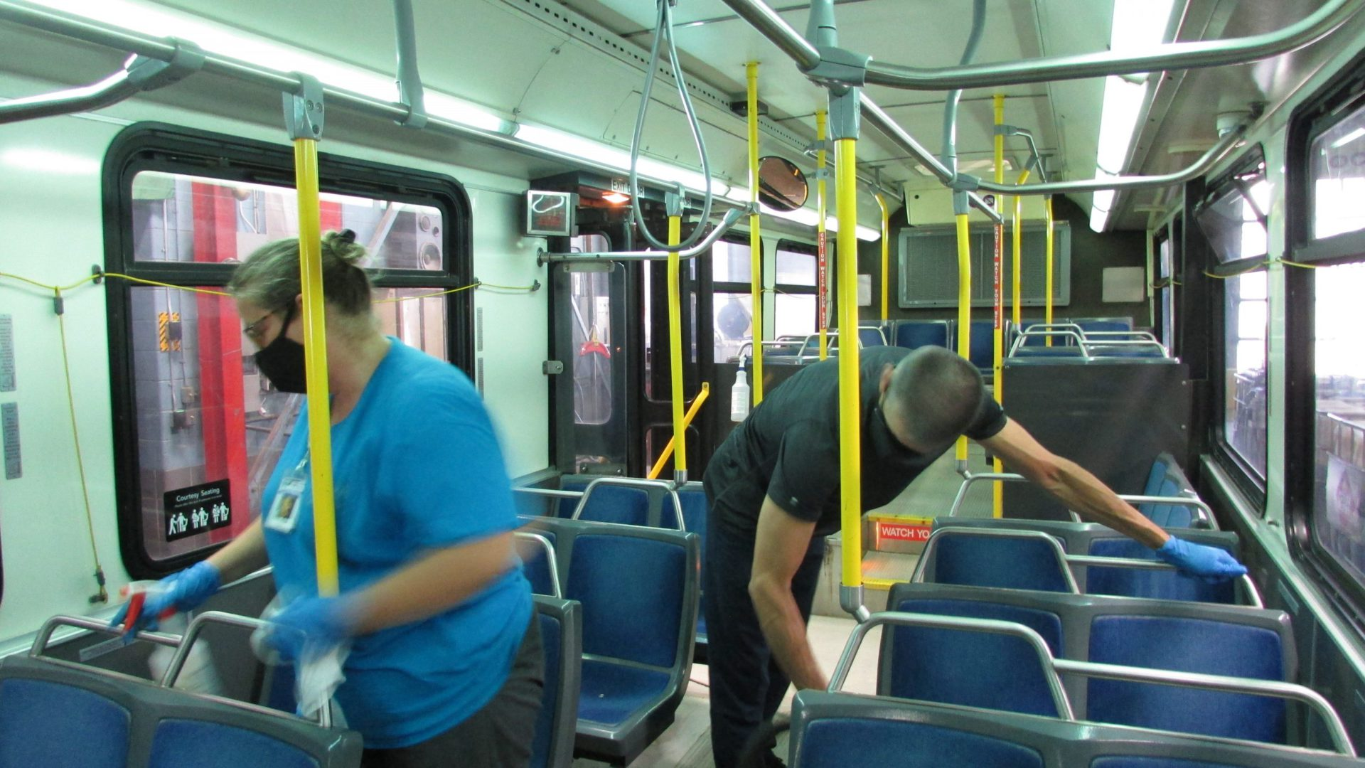 A cleaning crew sanitizes a bus.